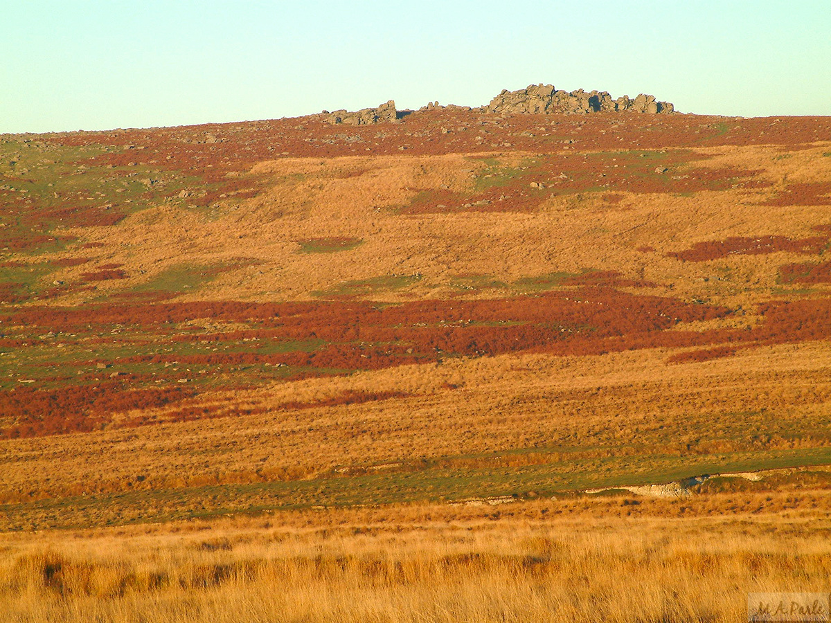 The setting sun gives a red glow to the slopes of Great Trowlesworthy Tor
